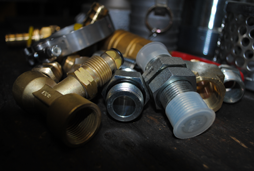 Brass and stainless steel hose fittings, two, four and six wire fittings, garden hose fitting, air hose fitting, AN fittings and adapters including a flat face adapter, JIC adapter, SAE adapter, two threaded pipe adapters, a British, German, Din and metric adapter and two compression adapters are shown here.
