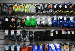 Picture of dozens of pairs of work gloves, sport gloves, hunting gloves, thermal gloves, leather gloves and deer skin gloves on our in-store display in our Erie, PA store.